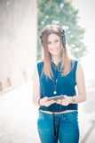 Música de escuta da mulher bonita nova do moderno Fotografia de Stock