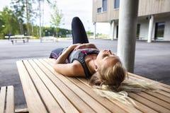 Música de escuta da mulher desportiva ao descansar no banco foto de stock
