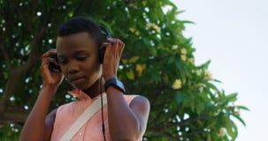 Música de escuta da mulher em fones de ouvido ao verificar o tempo em seu smartwatch 4k video estoque