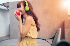 Música de escuta da mulher eufórico com música de escuta da mulher eufórico com fones de ouvido e comer a maçã vermelha ao lado d foto de stock