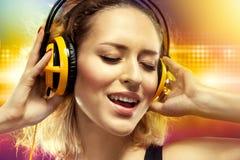 Música de escuta da mulher feliz com fones de ouvido Fotografia de Stock