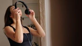 Música de escuta da mulher feliz nova com os fones de ouvido no movimento da dança em sua casa filme