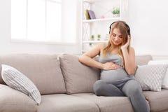 Música de escuta da mulher gravida nos auscultadores Fotos de Stock Royalty Free