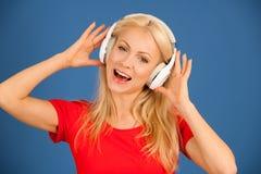 Música de escuta da mulher loura nova bonita sobre a cor vibrante b Foto de Stock Royalty Free