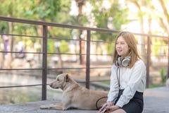 Música de escuta da mulher na linha com fones de ouvido de um smartphone fotos de stock royalty free