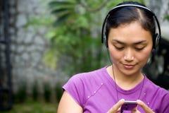 Música de escuta da mulher nova Imagem de Stock