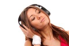 Música de escuta da mulher nova em auscultadores grandes Foto de Stock Royalty Free