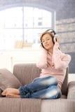 Música de escuta da mulher nova em casa Imagens de Stock Royalty Free