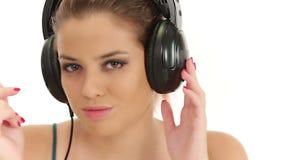 Música de escuta da senhora bonita em grandes fones de ouvido, olhando a câmera e fazendo beijos do sopro filme