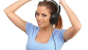 Música de escuta da senhora bonita em grandes fones de ouvido, olhando a câmera e fazendo beijos do sopro vídeos de arquivo