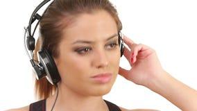 Música de escuta da senhora bonita nos grandes fones de ouvido, olhando a câmera video estoque