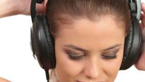 Música de escuta da senhora bonita nos grandes fones de ouvido, olhando a câmera vídeos de arquivo