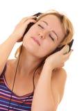 Música de escuta das mulheres bonitas nos auscultadores Imagens de Stock