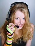 Música de escuta das mulheres novas nos auscultadores Imagens de Stock