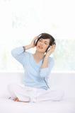 Música de escuta de assento da mulher através do fones de ouvido foto de stock