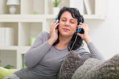 Música de escuta de sorriso bonita da mulher Imagem de Stock
