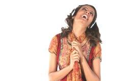 Música de escuta de sorriso da menina com telefones principais Foto de Stock Royalty Free