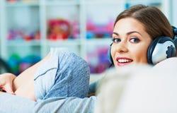 Música de escuta de sorriso da mulher nos auscultadores Imagem de Stock