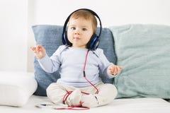 A música de escuta do bebê doce em fones de ouvido na condução postula imagens de stock