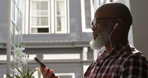 Música de escuta do executivo masculino superior no telefone celular 4k vídeos de arquivo