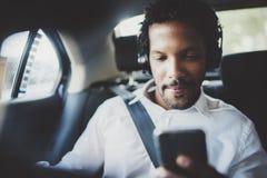 Música de escuta do homem africano considerável no smartphone ao sentar-se no assento traseiro no carro do táxi Conceito de joven imagens de stock royalty free