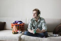 Música de escuta do homem ao dobrar a lavanderia no sofá fotografia de stock