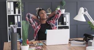 Música de escuta do homem de negócios relaxado em fones de ouvido no escritório filme