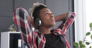 Música de escuta do homem novo através dos fones de ouvido no escritório video estoque