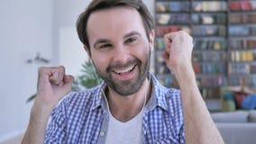 Música de escuta do homem ocasional feliz da barba em fones de ouvido e dança com alegria vídeos de arquivo
