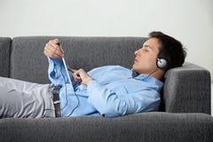 Música de escuta do homem relaxado na tabuleta de Digitas imagem de stock