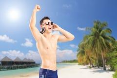Música de escuta do indivíduo feliz, em uma praia com palmas e cotta da casa de campo fotos de stock