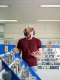 Música de escuta do indivíduo na loja cd Fotos de Stock Royalty Free