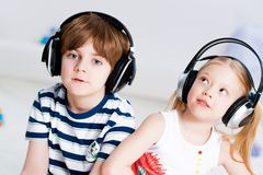 Música de escuta do irmão e da irmã com auscultadores imagem de stock