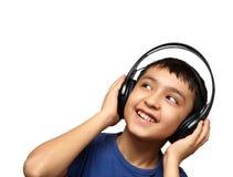 Música de escuta do menino nos auscultadores Imagens de Stock