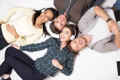 Música de escuta dos amigos multirraciais felizes foto de stock royalty free