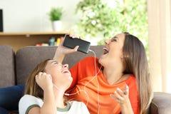 Música de escuta dos amigos ou das irmãs e canto Fotos de Stock Royalty Free