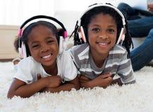 Música de escuta dos irmãos adoráveis Fotografia de Stock Royalty Free