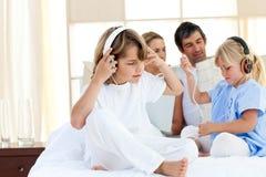 Música de escuta dos irmãos alegres com auscultadores Fotos de Stock