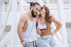 Música de escuta dos pares novos com fones de ouvido ao relaxar em Pebble Beach imagens de stock royalty free