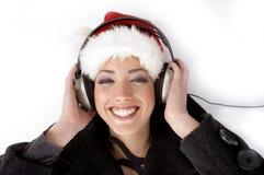 Música de escuta fêmea feliz e Natal desgastando Imagem de Stock Royalty Free