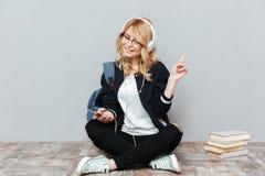 Música de escuta feliz do estudante fêmea no assoalho imagens de stock
