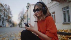 Música de escuta nos fones de ouvido, estilo urbano da moça bonito, assento adolescente do moderno à moda em um passeio na rua da filme