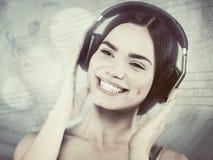 Música de la audiencia de la chica joven de la belleza con las auriculares Fotografía de archivo