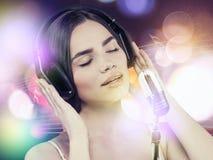 Música de la audiencia de la chica joven de la belleza con las auriculares Imagen de archivo libre de regalías