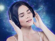 Música de la audiencia de la chica joven de la belleza con las auriculares Foto de archivo libre de regalías