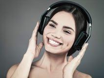 Música de la audiencia de la chica joven de la belleza con las auriculares Fotografía de archivo libre de regalías