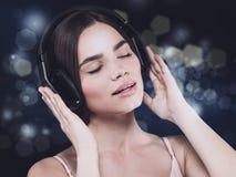Música de la audiencia de la chica joven de la belleza con las auriculares Foto de archivo