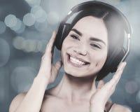 Música de la audiencia de la chica joven de la belleza con las auriculares Imagen de archivo