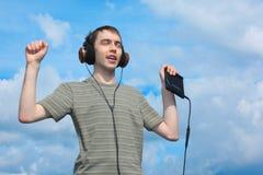 Música de los liistens del adolescente en los auriculares al aire libre Imagen de archivo libre de regalías