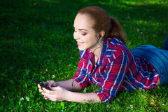 Música de mentira y que escucha del adolescente con el teléfono elegante en parque Foto de archivo libre de regalías